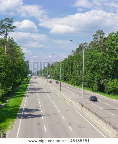 View of the motorway with lampposts traffic barriers pedestrian bridge and forest on both sides in summer day