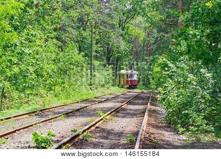 Old red tram at a tram line laid in the forest in summer