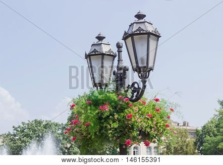 Old style street lamp and flowerpot with flowers on it on the background of a sky on a city street in summer day