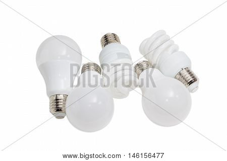Various energy saving electric lamps of different types - compact fluorescent lamps and light emitting diode lamps on a light background