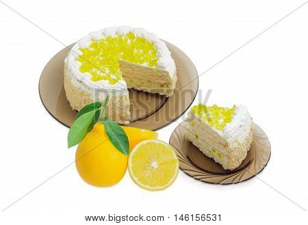 Piece of layered cake decorated with lemon jelly and cut cake on glass dishes and one whole and one cut fresh lemon on a light background