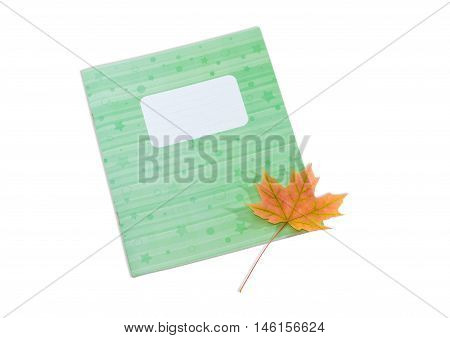 School exercise book with light green cover and one yellowed maple leaf on him on a light background