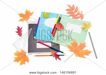 Several school exercise books school supplies and several yellow and red leaves on a light background