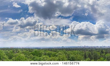 Sky with cumulus clouds over deciduous and coniferous forest and modern city in summer day