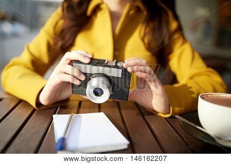 travel, tourism, photography, leisure and people concept - close up of young tourist woman or teenage girl with film camera and guidebook drinking cocoa at city street cafe terrace