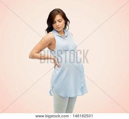 pregnancy, health, people and expectation concept - pregnant woman in bed touching her back and suffering from backache over beige background