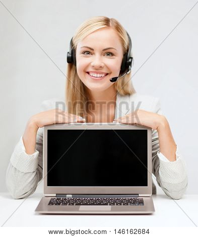 education, business, technology, advertisement and people concept - smiling young woman or helpline operator in headset with blank screen on laptop computer