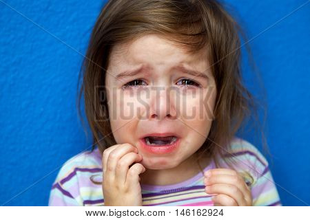 A very young girl stands in her pajamas crying big tears while scratching her Chicken Pox.