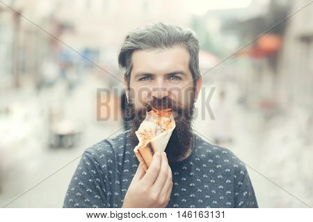 handsome sexy bearded young man hipster with long beard and mustache on serious hairy face eating pizza on street outdoor