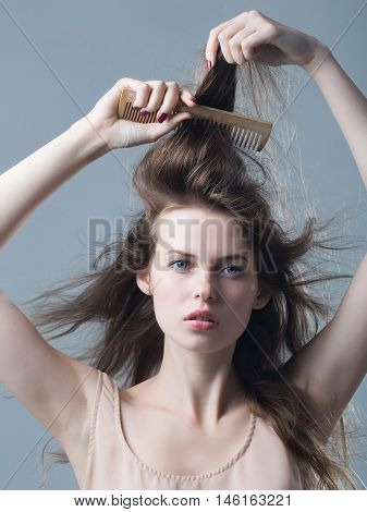young woman with slim sexy body pretty face and brunette long hair in dress holding hairbrush standing in studio on grey background