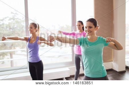 fitness, sport, training, gym and martial arts concept - group of happy women working out and fighting in gym