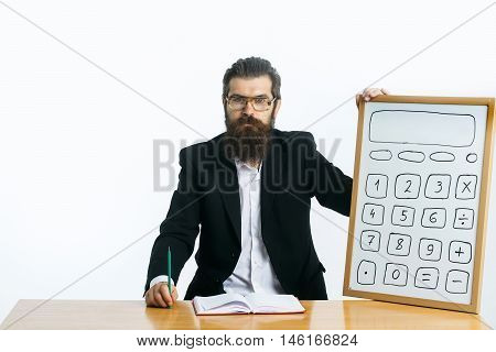 young handsome bearded man scientist or professor in teacher glasses with long beard holding board with calculator pencil and book or notepaper sitting at table isolated on white background