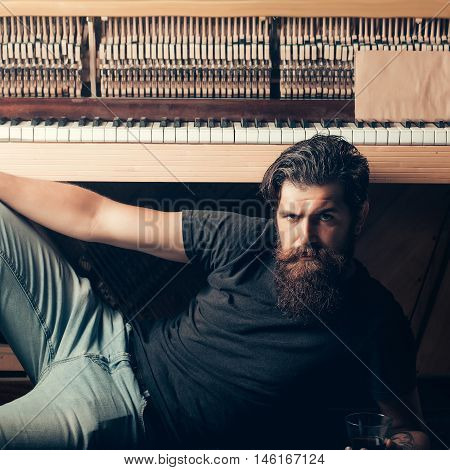 handsome bearded man with stylish hair mustache and beard on serious face drinking brandy or whiskey from glass near old wooden open piano with keyboard as musician with music book copy space