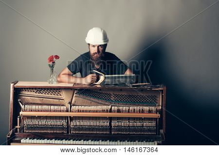 Man In Helmet Near Piano With Saw And Hammer