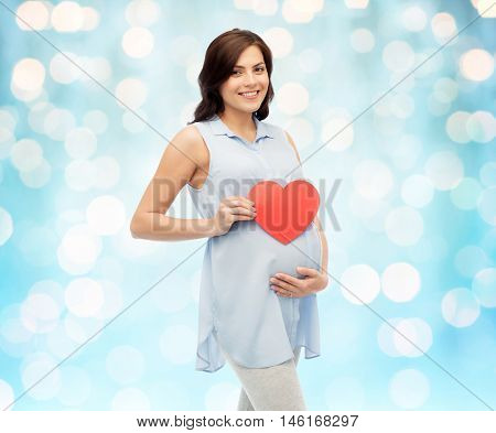pregnancy, love, people and expectation concept - happy pregnant woman with red heart shape touching her belly over blue holidays lights background