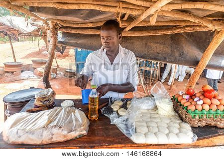 Uganda, Africa- March 31, 2016: Man preparing traditional Ugandan breakfast Rolex made with chapati and eggs