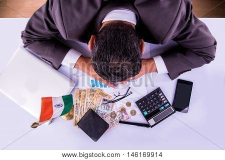 stressed indian businessman in head down pose while filling tax form or accounting with indian currency, calculator, laptop pen, money purse, spectacles