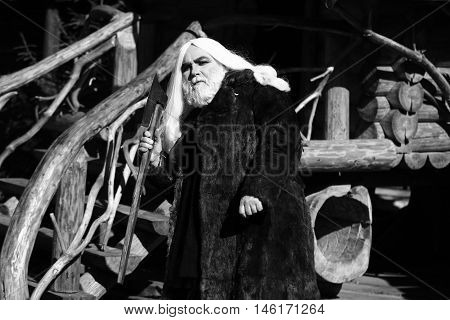 Brutal druid old man with long silver hair and beard in fur coat with axe in hand black and white on log house background