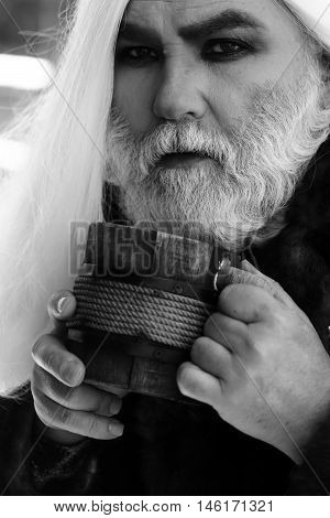 Druid old man with wrinkles long silver beard hair with wooden mug in hands black and white on grey background