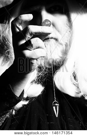 Old man wizard with long gray hair beard in black costume and hat for Halloween holding gem stone and silver pendant for hypnosis on wooden background black and white