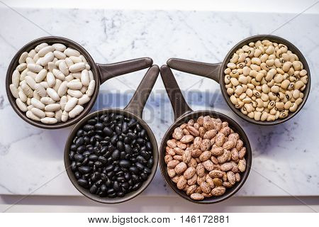 Beans variety/ different types of beans in ceramoc bowls on black wooden background
