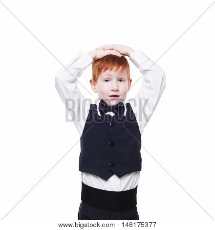 Little cute redhead boy in balck vest surprised and excited holds his head. Portrait of well-dressed sweet child in bow tie isolated on white background