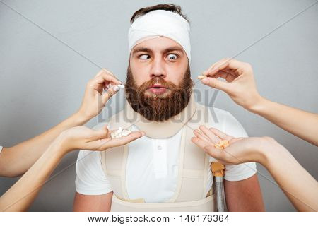 Suspicious freaky bandaged bearded man taking pills from doctors hands over gray background