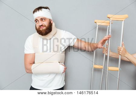 Sad depressed bandaged bearded man refuse to take crutches from female hands over gray background