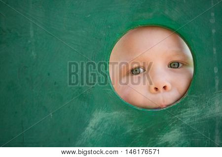 Closeup portrait of cute little toddler boy looking into green wooden frame at a playground. Curiosity exploration and leaning. Activities for children outdoors. Preschool daycare. Small boy playing