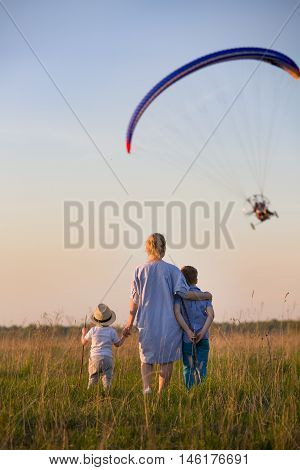 Back view on young woman toddler and kid boy standing in the sunny field and watching paraplane in the sky. Happy family walking on summer meadow and looking at paraplane. Lifestyle. Mother and sons