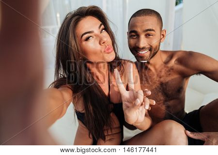 Young smiling couple in love making selfie while sitting at the beach bed and showing v sign