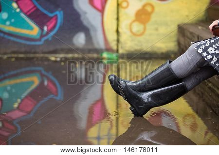 Woman in grey rubber boots sitting on the bench after rain. Pair of grey rubber boots in a big puddle with grafiti wall reflection. Fun after rain.