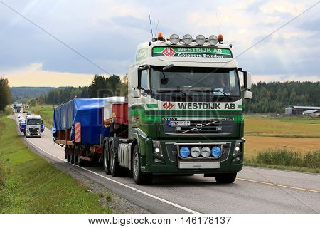 JAMSA FINLAND - SEPTEMBER 1 2016: Volvo FH semi truck of Westdijk AB hauls oversized industrial object in convoy with other wide load road transports among traffic in Central Finland.