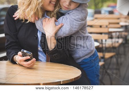 Portrait of cute kid boy hugging his mother on the street cafe in the city. Happy family outdoors. Mum and son smiling and hugging at the wooden table in a cafe.