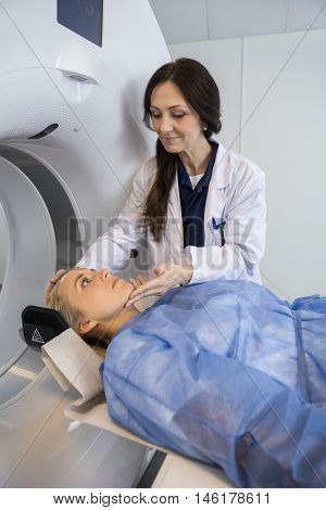 Doctor Adjusting Patient's Face Before MRI Scan