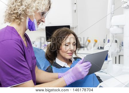 Assistant Showing Report To Female Patient On Digital Tablet
