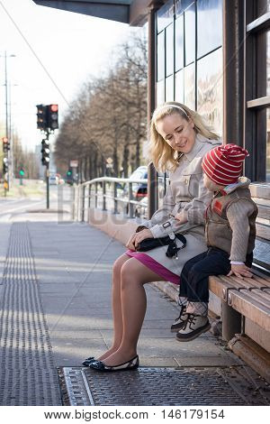 Beautiful young mother with her toddler son sitting on the bench on a bus stop and waiting for a bus. Happy family waiting for transport in the city centre.Woman with a cute boy outdoors.