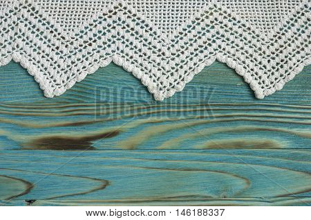 Handmade crocheted cotton organic blanket on wooden background. White original crochet lace frame. Knitted lace on colored wooden table