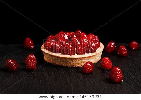 Tartlet with custard, fresh glazed raspberries, served on vintage stone surface. Dark rustic style.