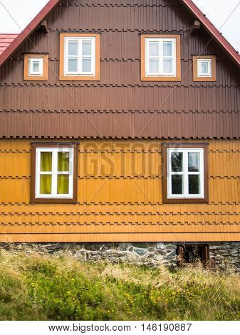 Authentic rustic yellow and brown mountain cottage front with windows and stones in Bohemian Forrest, Czech republic, Europe