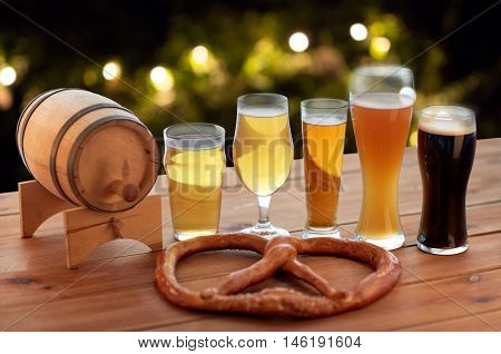 brewery, drinks and food concept - close up of different beer glasses, wooden barrel and pretzel on table over holidays lights background