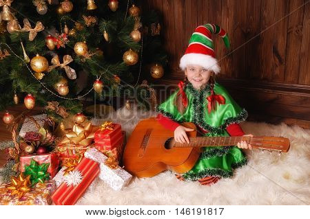 Little girl in suit of the Christmas Elf with a Guitar near Xmas fir-tree and holidays gifts.