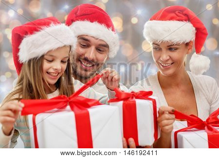 family, happiness, generation, holidays and people concept - happy family in santa helper hats with gift boxes sitting on couch at home