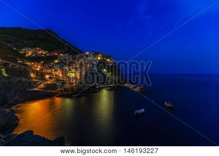Colorful traditional houses on a rock over Mediterranean sea after sunset at the dusk, Manarola, Cinque Terre, Italy, Ligurian Coast.