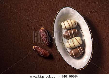 Ripen dates and premium date chocolates in a small bowl. An Arabic sweet and delicacy.