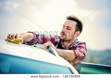Car wash.Man with a microfiber wipe the car polishing.