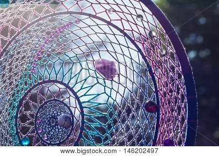 photo of a dreamcatcher made by hand with using threads beads and feathers rooster