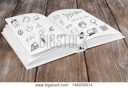 Book with icons on wooden background.