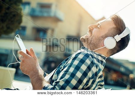 Young man sitting outdoors listening to music.He is enjoying the music.