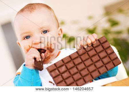 Baby boy eating chocolate.He is looking at camera.